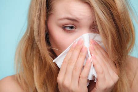 symptom: Flu cold or allergy symptom. Sick woman girl sneezing in tissue on blue. Health care.