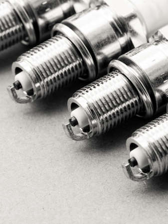 Auto service. Set of new car spark plugs as spare part of auto transportation on gray photo