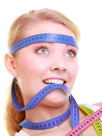 Time for diet slimming weight loss. Health care healthy lifestyle. Fit fitness woman with violet measure tapes around her head. Obsessed girl by body isolated photo