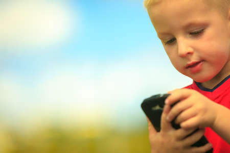 Little boy child kid  playing games on smartphone mobile phone outdoor. Technology generation. photo