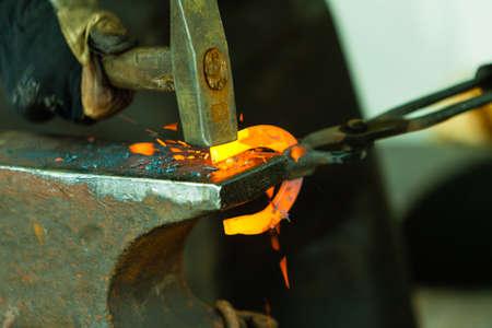 smithy: Fare elemento decorativo nella fucina sull'incudine. Martellare incandescente in acciaio. Fabbro forgia un ferro di cavallo caldo. Archivio Fotografico