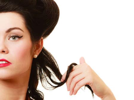 coquete: Estilo retro. Close up da mulher coquette brincando com o cabelo isolado. Menina morena Glamour com penteado pinup e maquiagem.