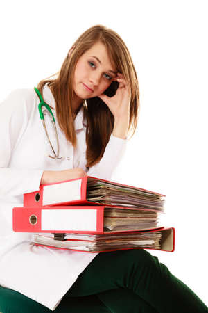 Medicine and paperwork. Tired overworked busy doctor woman with stack of folders with files documents isolated on white. photo