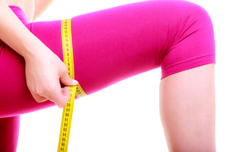 losing control: Time for diet slimming weight loss. Health care and healthy nutrition. Young fitness woman fit girl with measure tape measuring her thigh isolated on white Stock Photo