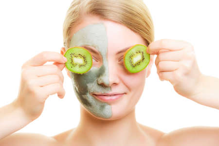 wellfare: Skin care. Woman in clay mud mask on face covering eyes with slices kiwi. Girl taking care of dry complexion. Beauty treatment