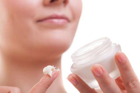 スキンケア。女性の顔のクローズ アップ。若い女性美人保湿クリーム分離を適用する乾燥顔色の世話します。美容トリートメント。