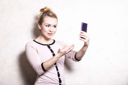 misunderstanding: Portrait of mad businesswoman texting on the mobile phone. Angry woman confused girl reading sms on smartphone. Misunderstanding. Indoor. Stock Photo