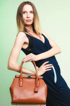 Elegant outfit  Stylish woman fashionable girl with brown leather handbag bag on green  Fashion and female beauty  photo