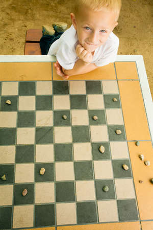 draughts: Draughts board game  Little boy clever child kid playing checkers thinking, outdoor in the park  Childhood and development