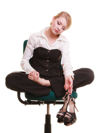 Break from work. Tired businesswoman with leg pain. Young woman massaging her feet on chair isolated on white. photo