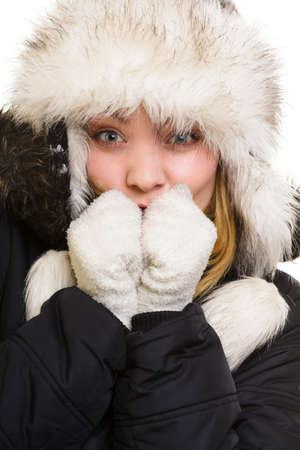 Winter vacation. Freezing girl in warm clothes. Young woman in fur hat warming her cold hands by breath isolated on white. photo