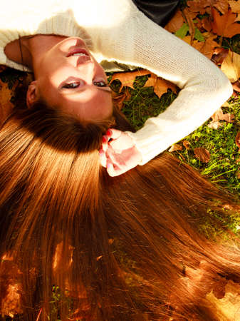 Fall lifestyle concept, harmony freedom. Woman portrait in autumn leaves. Girl with long hair having fun outdoor photo