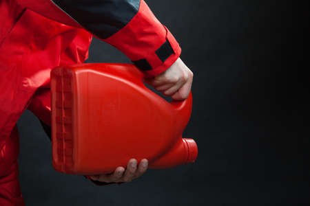 Closeup of male hands with petrol canister. Man industrial worker of gas station wearing red waterproof wind jacket holding oil can container on black. Power and energy industry. Studio shot. photo