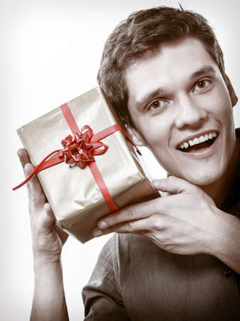 Holiday and special occasion. Young handsome man got golden present gift box with red ribbon isolated on white. Surprise. Studio shot. photo