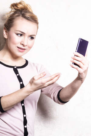misunderstanding: Portrait of mad businesswoman texting on the mobile phone  Angry woman confused girl reading sms on smartphone  Misunderstanding  Indoor