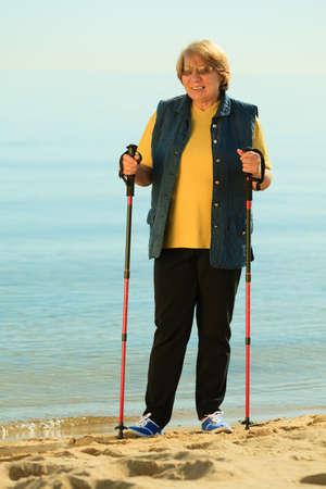 active mature lifestyle. senior nordic walking on a sandy beach sea shore. photo
