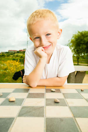 Draughts board game. Little boy clever child kid playing checkers thinking, outdoor in the park. Childhood and development photo