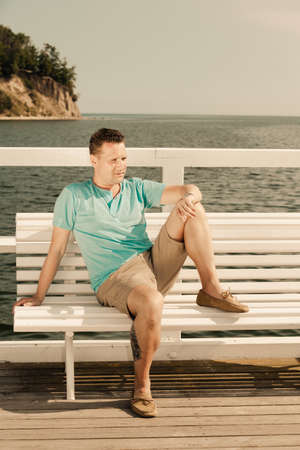 Happiness summer vacation and people concept. Fashion portrait of handsome man sitting in sun on bench sea landscape photo