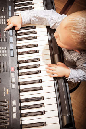 Happy childhood and music  Little boy child kid playing on the black digital midi keyboard piano synthesizer musical instrument indoor  photo