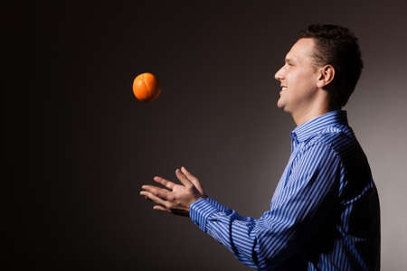 recommending: Diet and nutrition. Young smiling man throwing orange tropical fruit on gray. Happy guy recommending healthy food.