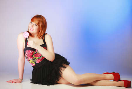 Full length sexy young woman holding candy. Redhair cute girl with sweet lollipop on blue. Temptation photo