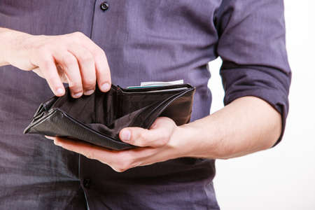 empty wallet: Empty wallet in male hands as symbol poverty and unemployment. Finance and poor economy. Isolated on white. Studio shot. Stock Photo