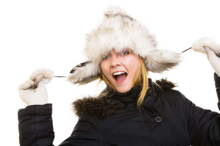 Winter vacation. Cheerful positive girl in warm clothes. Happy young woman in fur hat doing fun isolated on white. photo