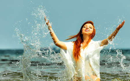 Vacation. Girl splashing water on the coast. Young woman having fun relaxing on the sea. Summertime. photo