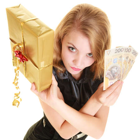 Happy smiling blonde girl young woman holding golden christmas gift box and polish currency money banknote. Holidays time for gifts. photo
