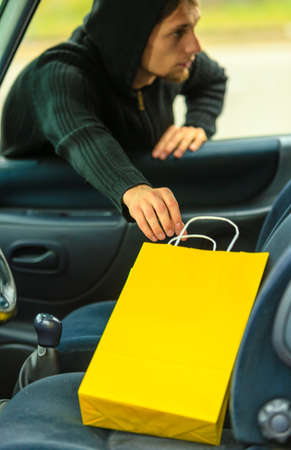 breakin: Transportation, crime and ownership concept - thief stealing shopping bag from the car