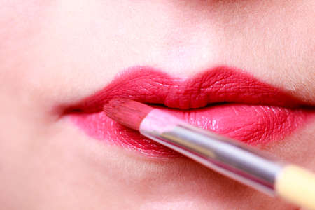 makeover: Cosmetic beauty procedures and makeover concept. Closeup part of woman face red lips. Make-up artist applying lipstick with accessories tools.