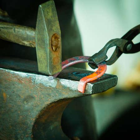 smithy: Fare elemento decorativo nella fucina sull'incudine. Martellare in acciaio incandescente. Fabbro forgia un ferro di cavallo caldo. Archivio Fotografico