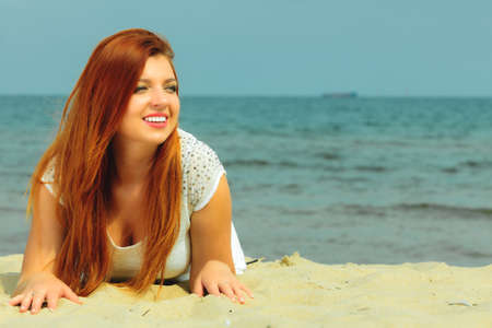 redhaired: Holidays, vacation travel and freedom concept. Beautiful redhaired happy girl on beach, portrait