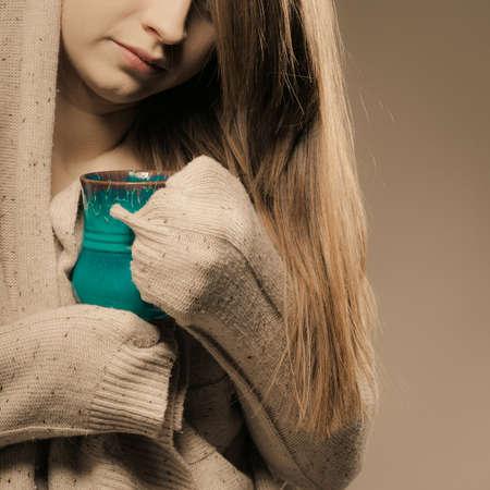Hot beverage. Closeup of girl drinking cup mug of drink tea or coffee. Woman warming herself photo