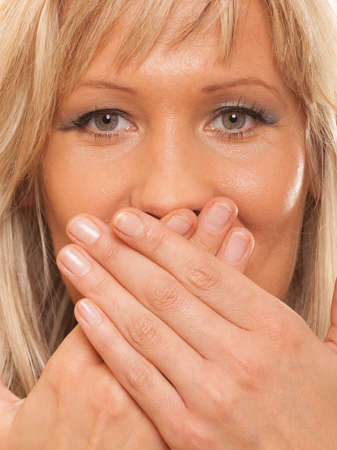 Speak no evil concept. Surprised woman face, covering her mouth with hands isolated photo