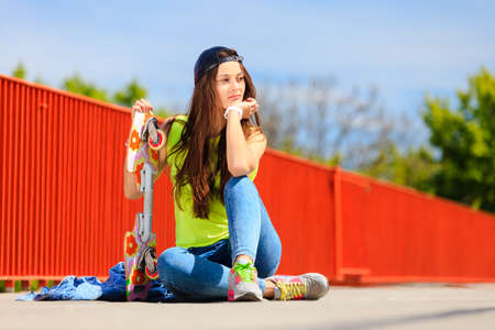 cool girl: Summer sport and active lifestyle. Cool teenage girl skater sitting with skateboard on the street. Outdoor. Stock Photo