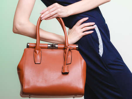 closeup: Elegant outfit. Closeup of brown leather bag handbag in hand of stylish woman fashionable girl on green. Female fashion.