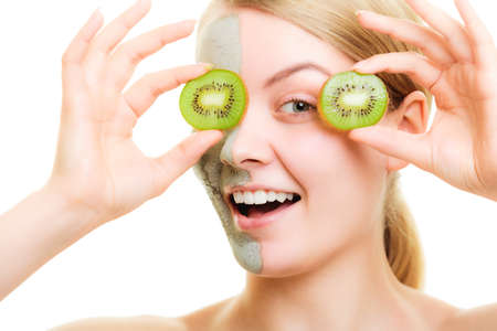 wellfare: Woman in clay mud mask on face holding slices of kiwi fruit isolated Stock Photo