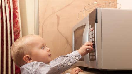 microondas: El niño hijo niño que juega con temporizador de horno microondas utensilios de cocina en la cocina doméstica como en casa.