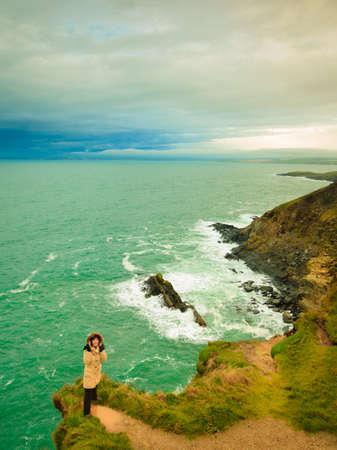 irish landscape: Woman tourist standing on rock cliff by the ocean Co. Cork, Ireland Stock Photo