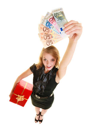 Happy smiling blonde girl young woman holding red christmas gift box and euro currency money banknotes. Holidays time for gifts. photo
