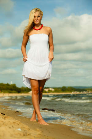 Beautiful girl in white dress walking on beach photo