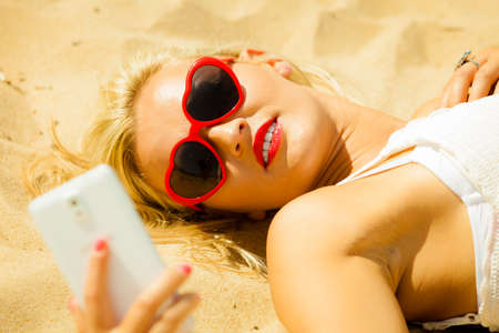 Young woman with smartphone mobile cell phone on beach photo