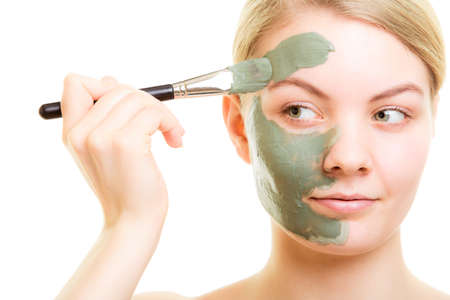 wellfare: Skin care. Woman applying with brush clay mud mask on face isolated. Girl taking care of dry complexion. Beauty treatment.