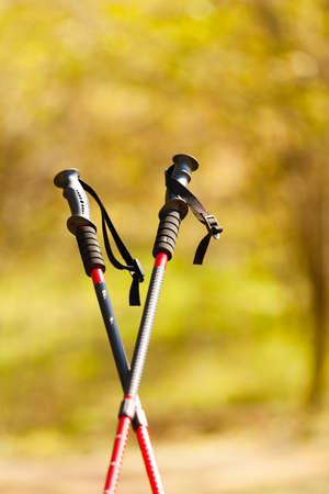 Nordic walking-apparatuur. Close-up van rode stokken in het park of bos. Actieve en gezonde leefstijl.