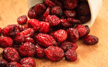 cranberry fruit: Healthy high fiber foods, organic nutrition. Close up dried cranberries cranberry fruit in bowl on wooden table. Stock Photo