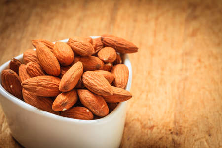 Healthy food, good for heart health.  Almonds in white bowl on wooden old rustic table background photo