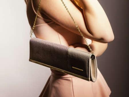 Female elegance. girl young woman holding in hand elegant handbag bag luxury accessory on gray