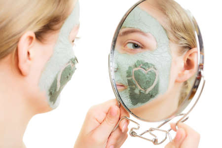wellfare: Skin care. Woman in clay mud mask on face with heart symbol of love on cheek looking in the mirror. Girl taking care of dry complexion.