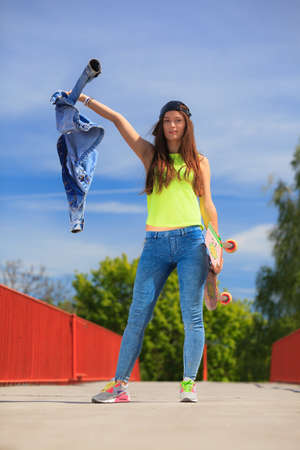 Summer sport and active lifestyle. Cool teenage girl skater\ with skateboard on the street. Outdoor.